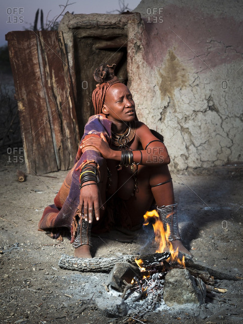 Africa - May 31, 2014: Himba woman in a blanket warming herself by a campfire
