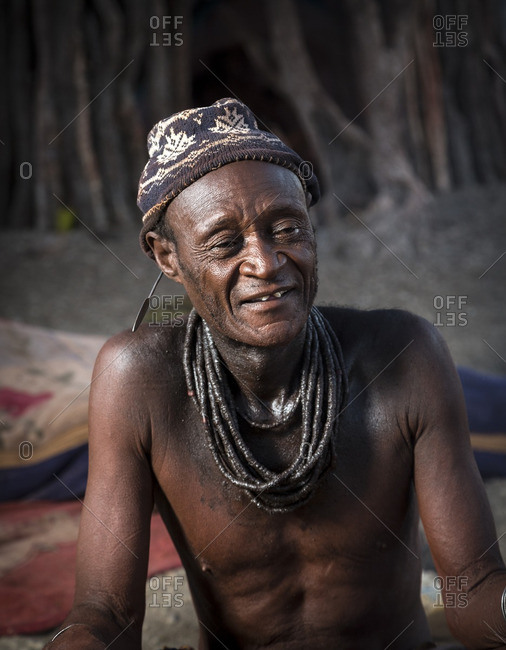 Africa - May 31, 2014: A traditionally dressed Himba man in beanie sitting near campfire