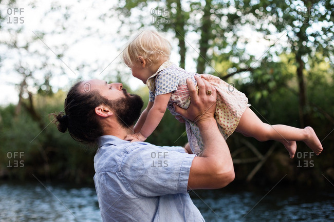 Father lifting baby into the air on a river