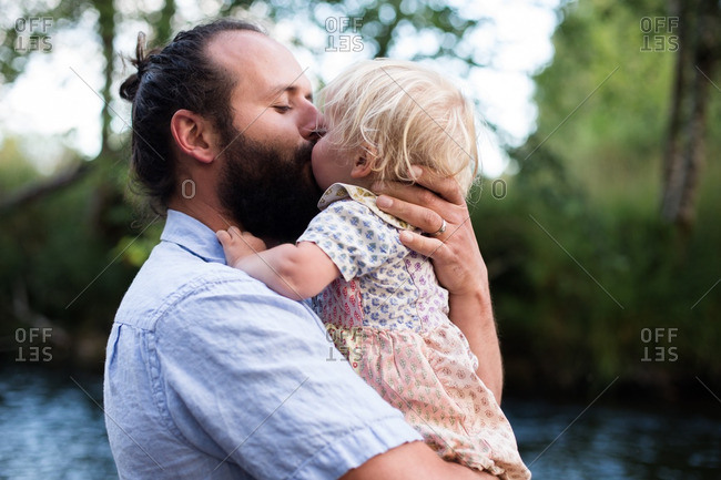 Father kissing baby girl on a river
