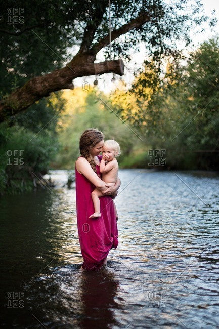 Woman standing under a tree in a river with their baby