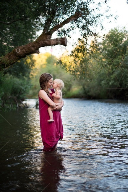 Woman kissing her baby on a river