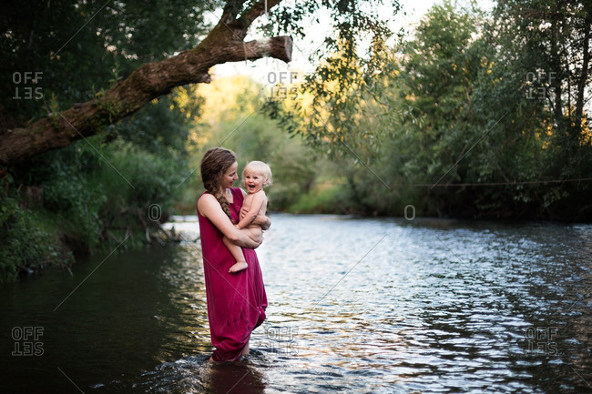 Woman holding her smiling baby on a river