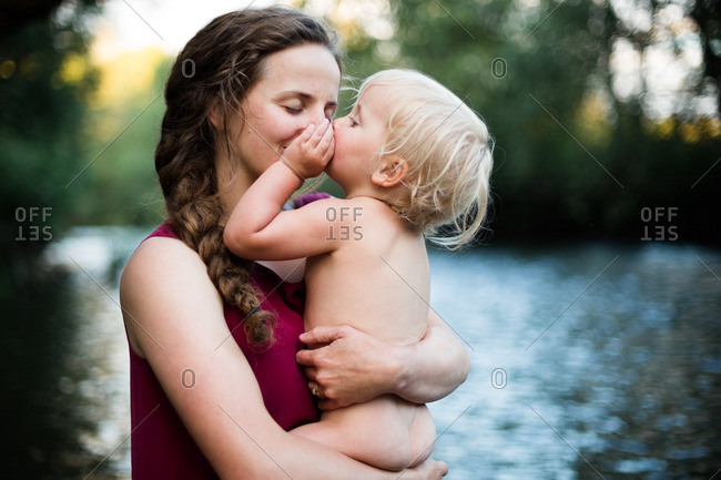 Baby kissing her mom's nose on a river