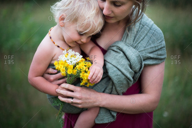 Mother holding toddler with handful of wildflowers