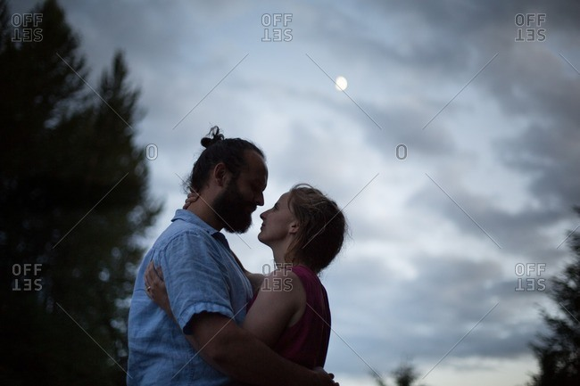 Loving couple embraced under a full moon