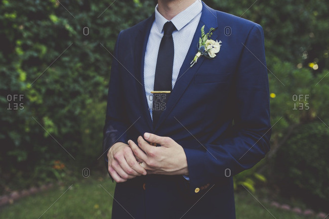 Groom standing outside twirling his wedding ring