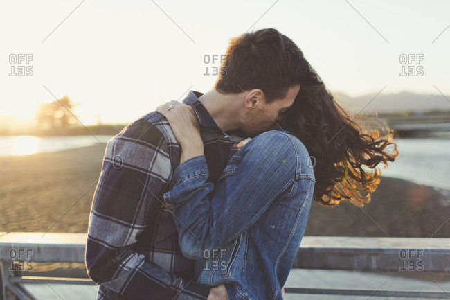 Newly engaged couple kissing outdoors