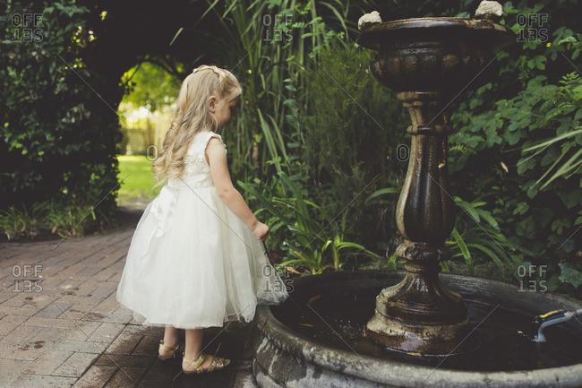Flower girl looking at fountain