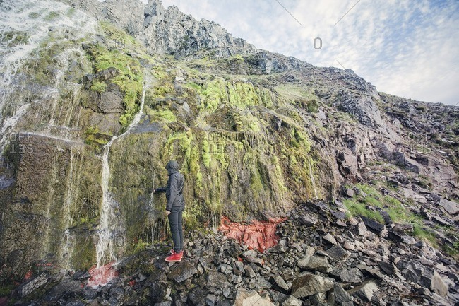 Person touching water flowing down cliff in Iceland