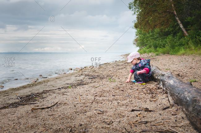 Little girl sitting on a beach wearing a raincoat