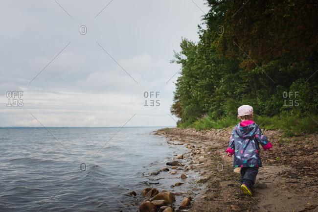 Little girl walking on a beach wearing a raincoat
