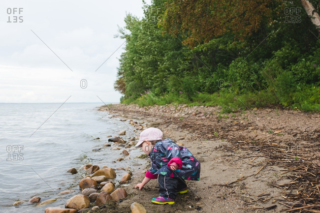 Little girl on a grabbing sand on a beach wearing a raincoat