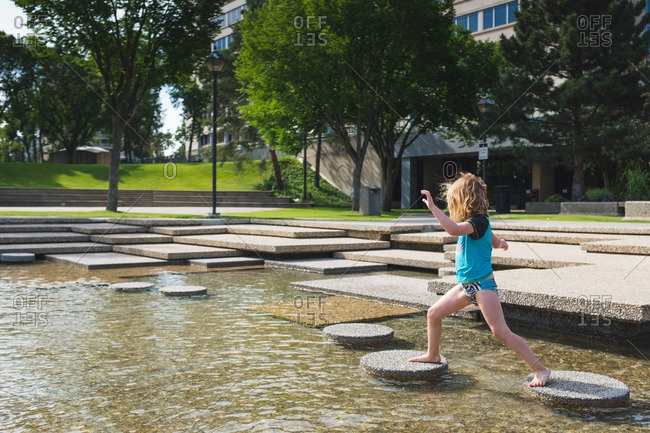 Little girl walking on stepping stones in a pond