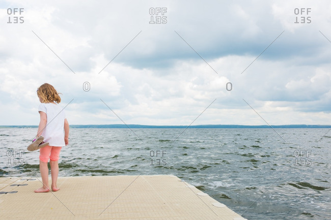 Little girl standing barefoot on platform by the ocean
