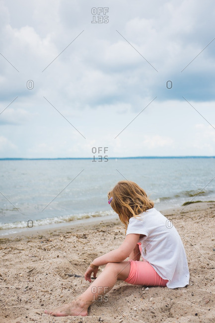 Little girl playing in sand on a beach