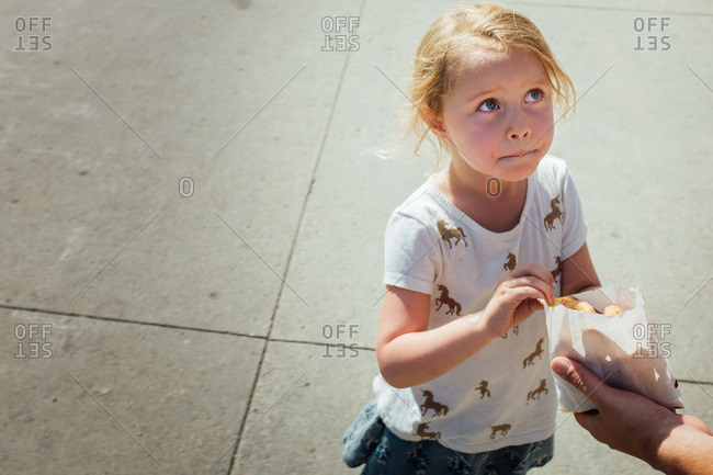 Little girl grabbing snack from a bag
