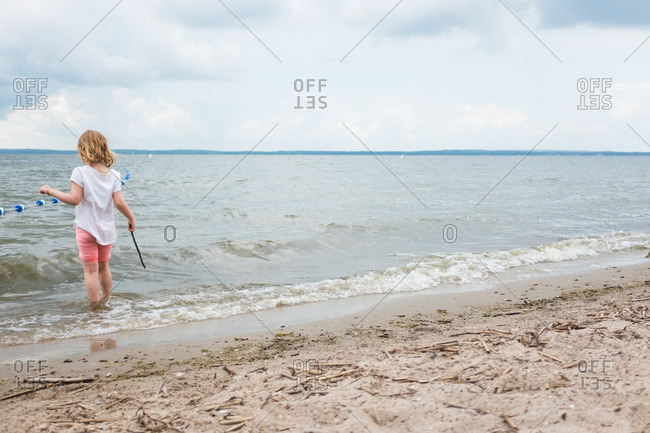 Little girl playing with a stick in the waves on a beach