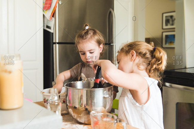 Two girls mixing muffin batter in a bowl