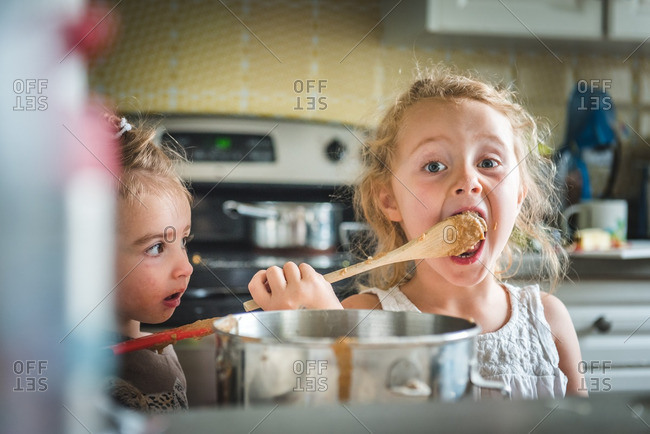 Little girl licking batter off spoon while baking