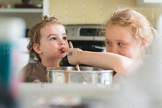 Little girl sucking batter off of sister's finger while baking