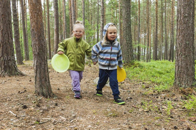 4 year old brother and sister walking with their plastic discs through the woods, Sweden