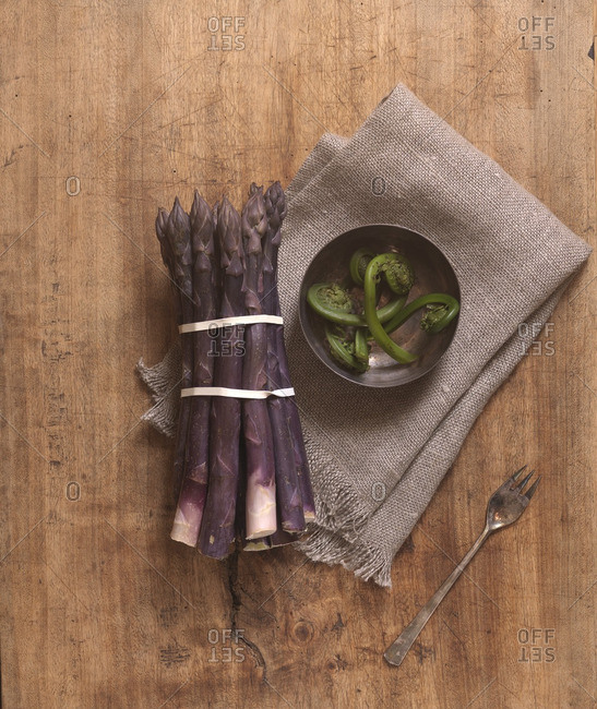 Overhead View of Bunch of Purple Asapragus and Bowl of Fiddleheads with Old Fork