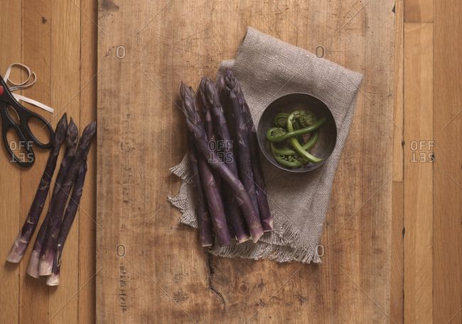 Overhead View of Purple Asparagus with Bowl of Fiddleheads on Wooden Board