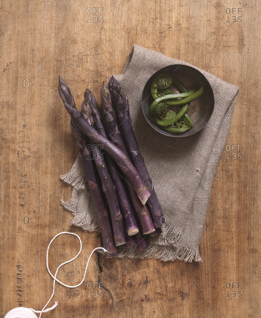 Overhead View of Bunch of Purple Asparagus with Bowl of Fiddleheads on Wooden Board with Twine