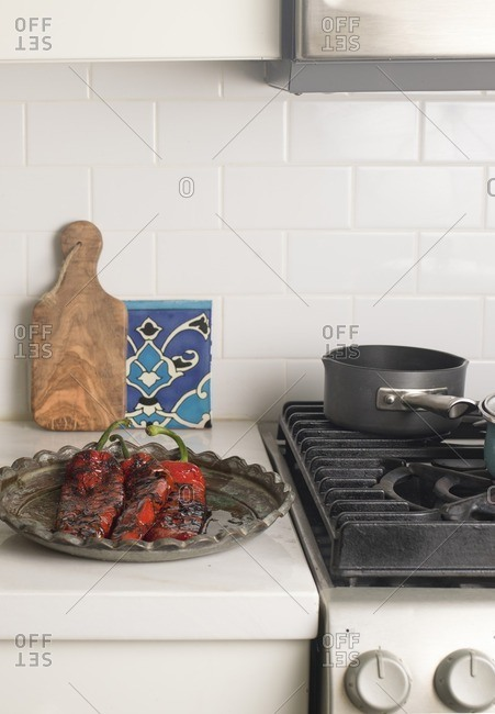 Platter of Roasted Red Peppers on Kitchen Counter with Small Bread Board and Tile