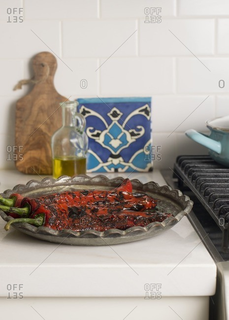 Platter of Roasted Red Peppers on Kitchen Counter with Bottle of Olive Oil