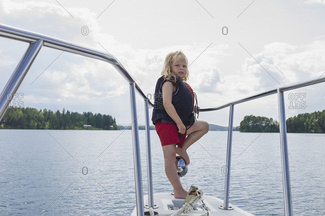 Boy Standing on Nose of Boat on Lake, Sweden