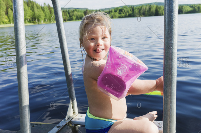 Girl with Down Syndrome wearing Water Wings Sitting on Jetty of Lake, Sweden