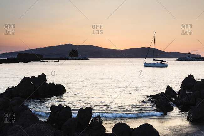 Silhouette of lava rocks and moored sailboat at sunset with Faial Island in the background in Madalena, Pico Island, Azores