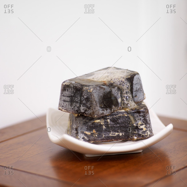 Two Artisanal Bars of Soap Stacked in White Soap Dish