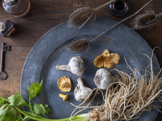 Overhead view of pewter plate with wild mushrooms, garlic and celery on wooden table with old key, bottles and dried bullrushes