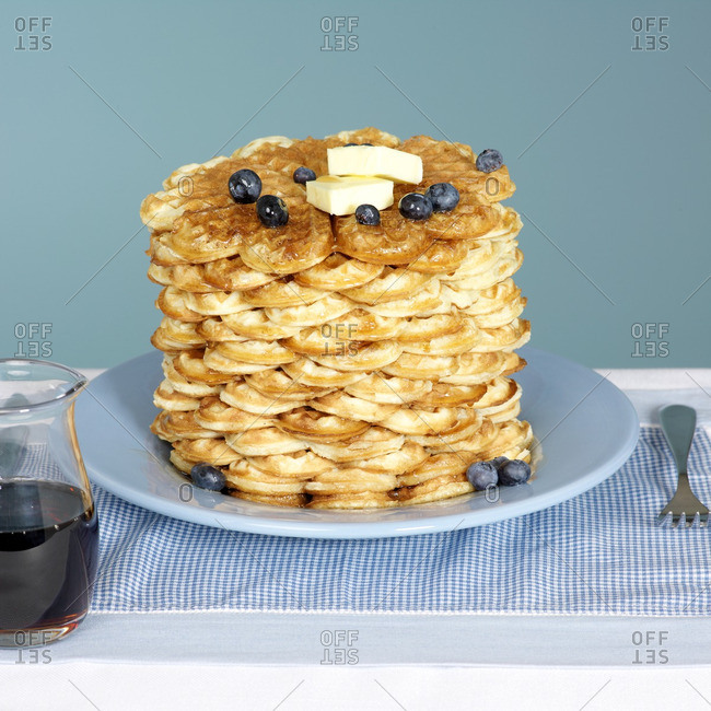 Stack of Waffles on Blue Plate with Butter and Blueberries and Maple Syrup in Jug on the Side