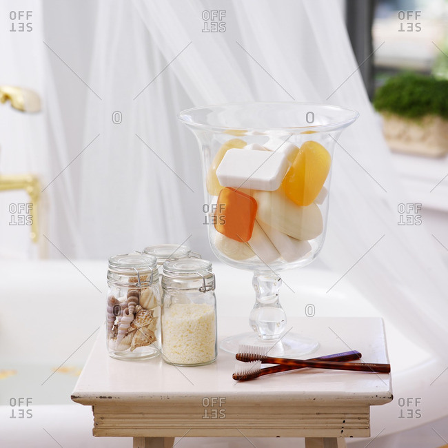Side Table in Bathroom with Jars of Soap, Seashells, Bath Salts and Toothbrushes