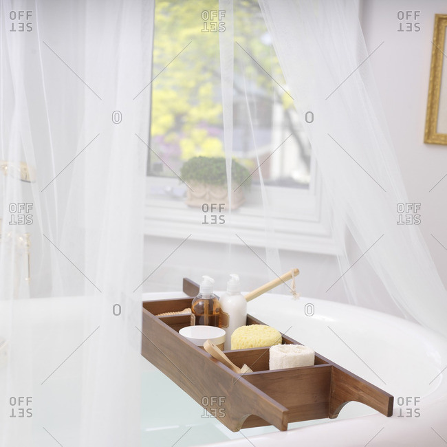 Bath Caddy on Bathtub Filled with Bath Items