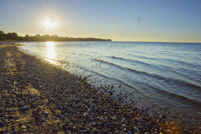Pebble beach with Sun in Summer, Sunset, Dronningmolle, Hovedstaden, Baltic Sea, Zealand, Denmark