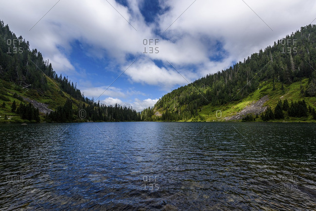 Scenic view of lake and green landscape against cloudy sky