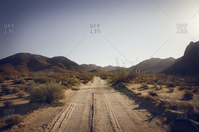 Scenic view of dirt road against clear sky on sunny day