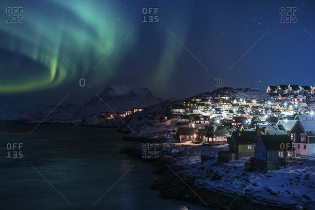 Illuminated houses by sea against sky