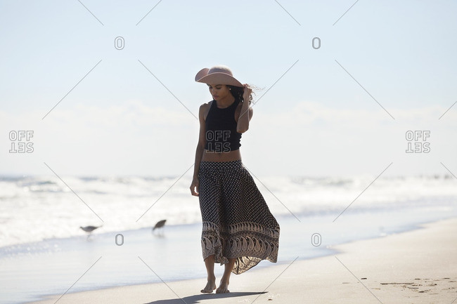 Woman in sun hat walking at shore on sunny day