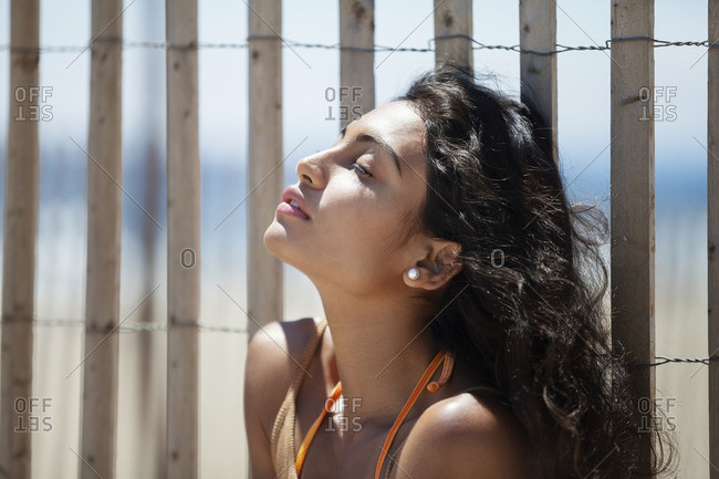 Relaxed woman sitting against fence at beach
