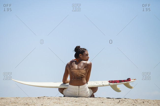 Rear view of woman with surfboard sitting at beach