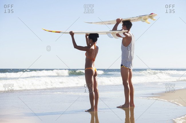 Couple carrying surfboard on head while standing at beach