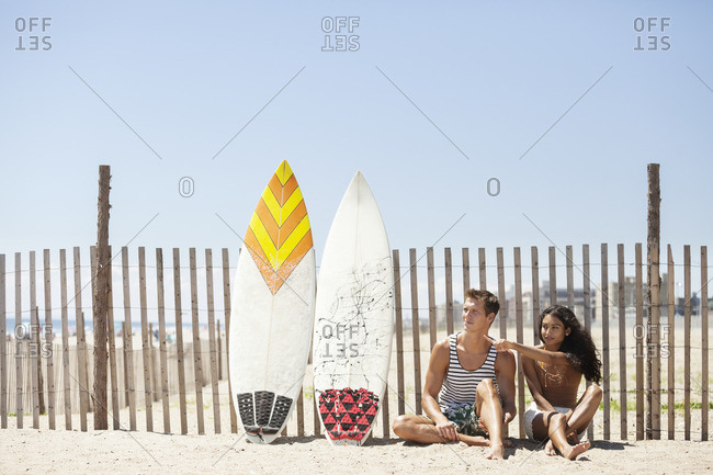 Woman pointing while sitting with boyfriend on sand against fence