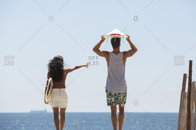 Woman pointing while standing with boyfriend at beach