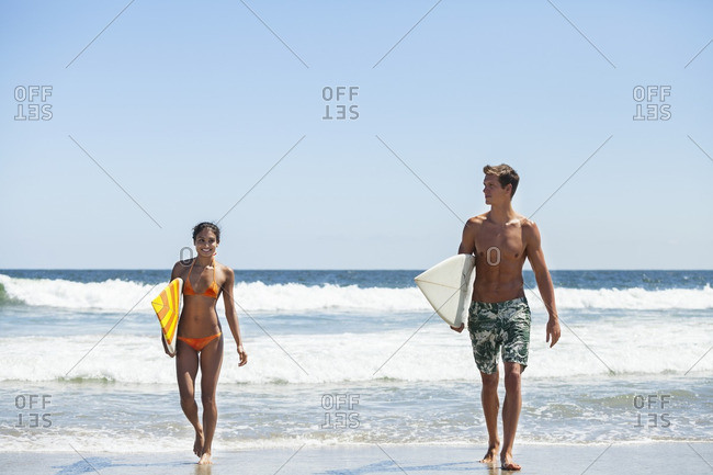 Happy couple carrying surfboard while walking at beach against clear sky